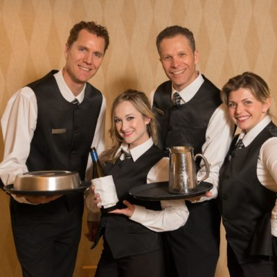 Vancouver's Singing Servers feature vocalists dressed in the same attire as the serving staff embedded with the other waiters. The singers would interact with the guests performing simple server duties to establish their characters. One of the servers would begin to hum a classic doo-wop song to himself. Another begins to clink glasses in a rhythmic manner…a third begins to snap her fingers. Suddenly another waiter begins to sing and a musical call & response takes place across the room as wonderment sweeps over the ballroom. Each of these musical elements come together as the Singing Servers move amongst the guests. The group breaks into a four part of a cappella sounds of Huey Lewis'